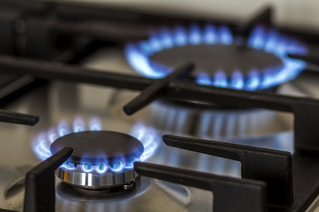 Natural gas burning on kitchen gas stove in the dark. Panel from steel with a gas ring burner on a black background, close-up shooting